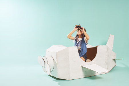 Foto de Little cute girl playing with a cardboard airplane. White retro style cardboard airplane on mint green background . Childhood dream imagination concept . - Imagen libre de derechos
