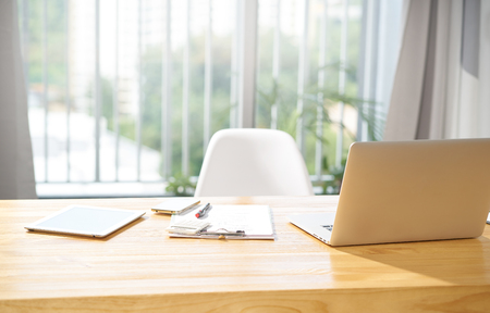 Photo for Empty workspace office with laptop,digital tablet,smartphone,note and pen , morning scene . - Royalty Free Image
