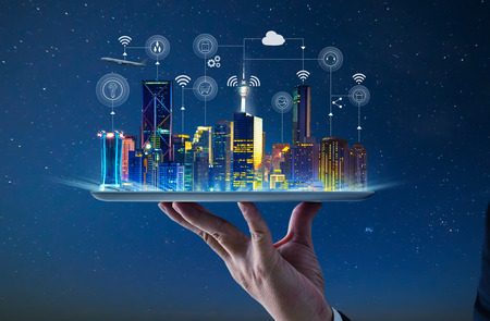 Foto de Waiter hand holding an empty digital tablet with Smart city with smart services and icons, internet of things, networks and augmented reality concept , night scene . - Imagen libre de derechos