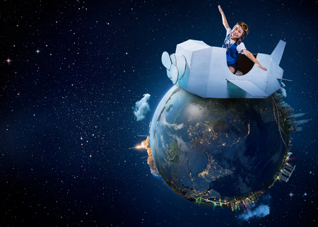 Foto de Little cute girl playing with a cardboard airplane with Earth planet background .Childhood dream imagination concept . .Extremely detailed image - Imagen libre de derechos