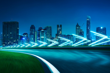 Photo pour Motion blurred racetrack,cityscape night scene cold mood. with arrow light Effects. - image libre de droit