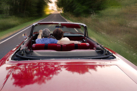 Photo pour A middle-aged couple snuggle together as they zoom down a county road in a classic red convertable, perhaps on a Sunday drive as they enjoy the experience and each other - image libre de droit