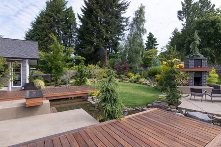 Photo pour Back yard of a contemporary Pacific Northwest home featuring a deck a spanning creek-like water feature with a landscaped lawn and custom patio fireplace in the background. - image libre de droit