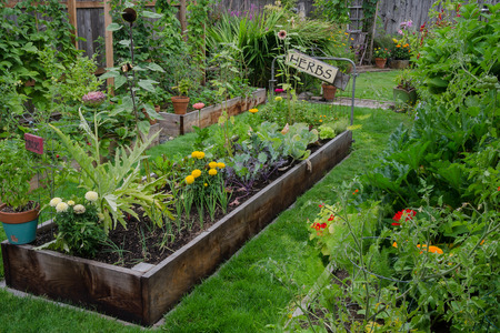 A raised bed filled with herbs and vegetables is nestled in the center of two other narrow gardens. A rustic, delightful sign adds and artistic accent.