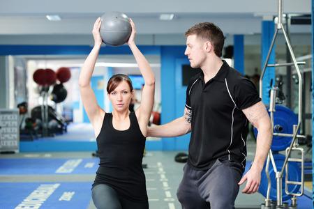 Foto de Personal trainer helping young woman in gym - Imagen libre de derechos
