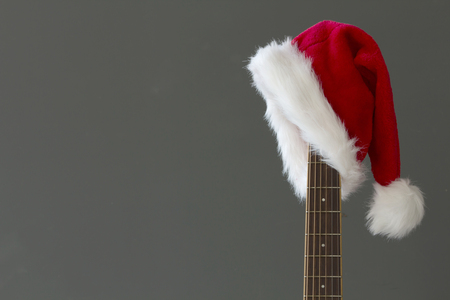 Photo for Red Christmas hat on guitar with grey background, Merry Christmas - Royalty Free Image