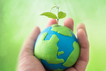 Foto de globe on hand with plant, safe the world , CSR Abbreviation or Corporate Social Responsibility concept - Imagen libre de derechos