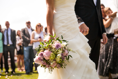 Photo pour Moment in wedding,  bride and bridegroom holding hands with bouquet and wedding guests in background - image libre de droit