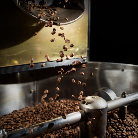 Foto de The freshly roasted coffee beans from a coffee roaster being poured into the cooling cylinder. Frozen moment. - Imagen libre de derechos