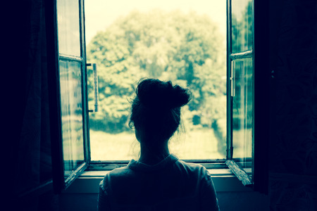 Photo for Woman looking through the window on the garden or forest in the countryside. Vintage filter. Blue tone. - Royalty Free Image