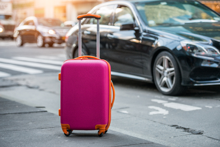 Foto de Luggage bag on the city street ready to pick by airport transfer taxy car. - Imagen libre de derechos