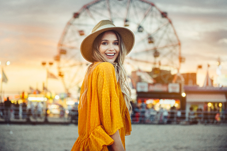 Photo pour Beautiful exited smiling tourist woman having fun at amusement park at hot summer day trip on the beach. - image libre de droit