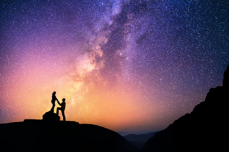 Foto de Romantic couple standing together holding hands in the mountains. Beautiful Milky Way galaxy on the background. - Imagen libre de derechos