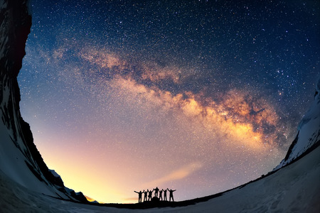 Photo pour Teamwork and support. A group of people are standing together holding hands against the Milky Way in the mountains. - image libre de droit