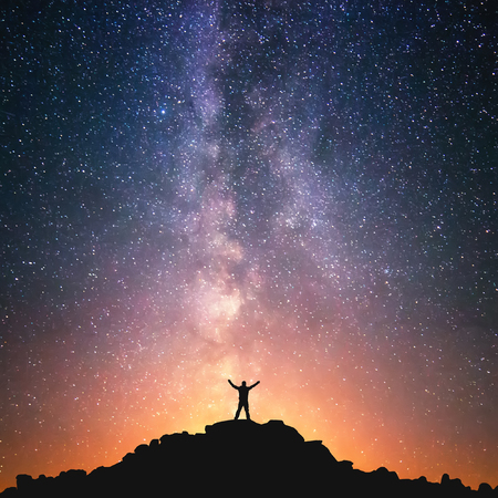 Photo for Man and the Universe. A person is standing on the top of the hill next to the Milky Way galaxy with his hands raised to the air. - Royalty Free Image