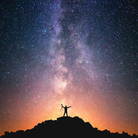 Foto de The Man and the Universe. A person is standing on the top of the hill next to the Milky Way galaxy with a tripod in his hands. - Imagen libre de derechos