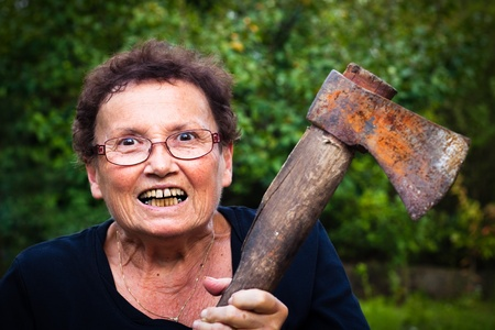 Crazy senior woman holding axe.
