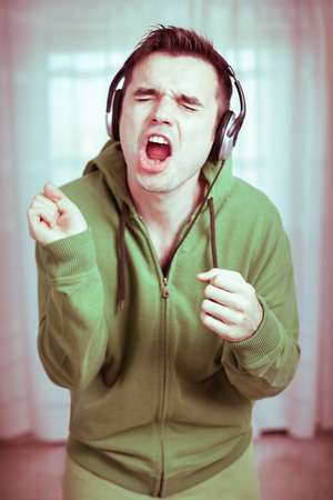 Photo for Crazy casual young man with headphones singing. - Royalty Free Image