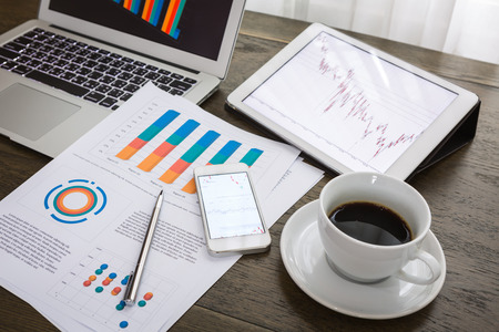 Laptop, tablet, smartphone and coffee cup with financial documents on wooden table