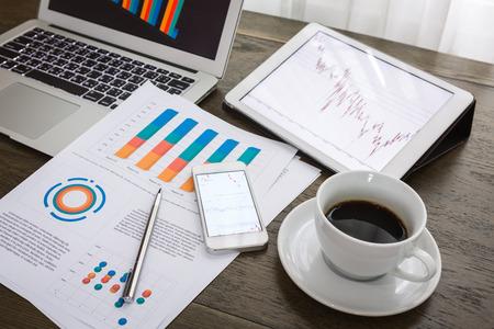 Foto de Laptop, tablet, smartphone and coffee cup with financial documents on wooden table - Imagen libre de derechos