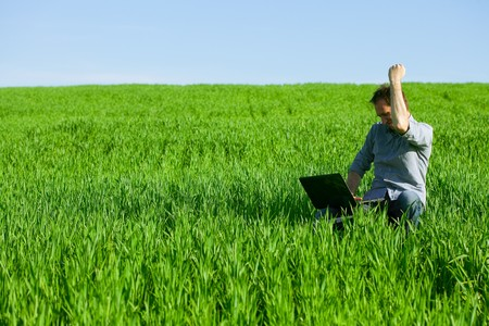 Photo pour Young man using a laptop outdoors - image libre de droit