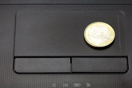 laptop keyboard and coin euro