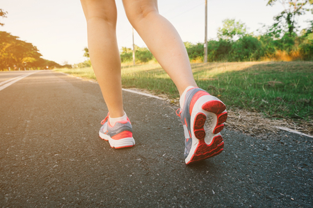 Photo pour Young lady running on road closeup on shoe., at time sunset. - image libre de droit