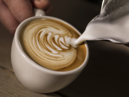 Foto de hand of barista making latte or cappuccino coffee pouring milk making latte art   - Imagen libre de derechos
