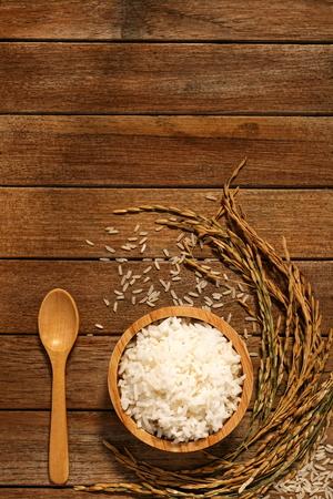 Foto de Jasmine rice in wood bowl and paddy rice on a brown wooden background beautiful Thai food - Imagen libre de derechos