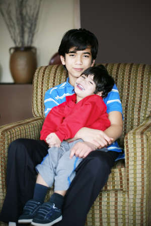 Big brother holding his younger sibling with cerebral palsy