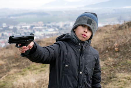 Photo for Young boy with angry face and gun - Royalty Free Image