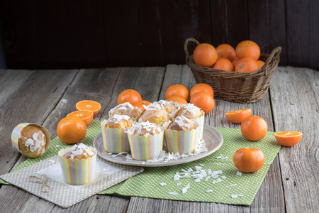 Photo for Mandarin muffins with coconut slices with lots of tangerines on old table - Royalty Free Image