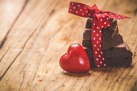 Photo pour Chocolate with ribbon and heart on St. Valentine's day love. - image libre de droit
