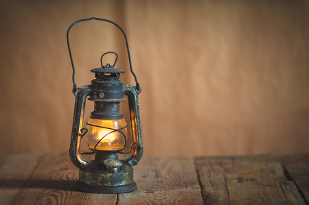 Foto de vintage kerosene oil lantern lamp burning with a soft glow light in an antique rustic country barn with aged wood floor - Imagen libre de derechos
