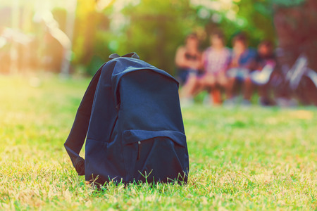 Photo pour Blue school backpack standing on green grass with students in background - image libre de droit