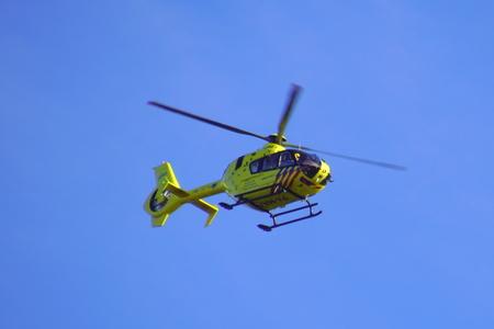 Foto de Almere, Netherlands - October 5, 2018: Dutch Ambulance Helicopter (Lifeliner 1) flying by against a clear blue sky. - Imagen libre de derechos