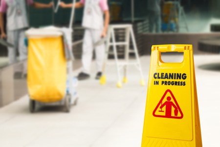 Foto de The warning signs cleaning in progress in the building and the janitorial mop bucket car parked and the maid working in the back. To remind people to walk safely. - Imagen libre de derechos