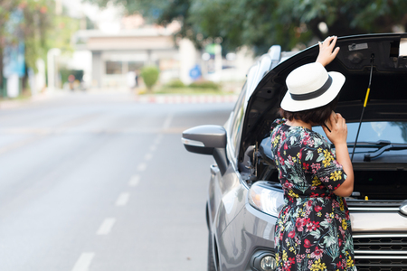 Foto de Asian women are using a smartphone to call the insurance company to see the car parked waiting to repair the side. - Imagen libre de derechos