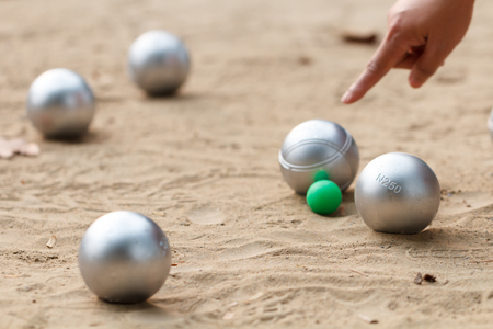 Photo pour boule ball or petanque in match with hand of female boule point in back - image libre de droit