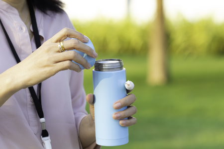 Photo pour Woman hand holding stainless steel water cylinder with copy space, concept of plastic free. - image libre de droit