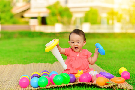 Photo pour Cute Asian baby playing with toys in playground - image libre de droit