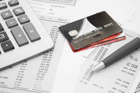 Photo pour Close up of a credit cards with credit card statements, pen and calculator - image libre de droit
