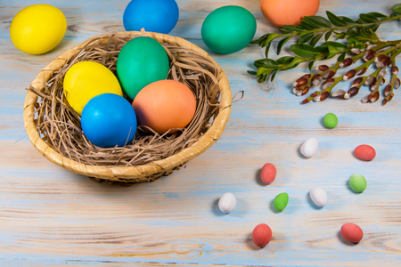 Photo for Easter eggs in a wooden basket, painted in different color on a blue background with a place for the inscription next to chokolate candy and green twigs - Royalty Free Image