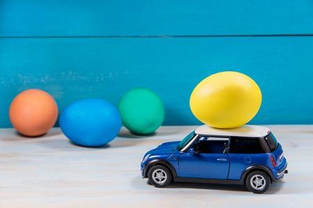 Photo pour Easter egg in toy car on a blue background - image libre de droit