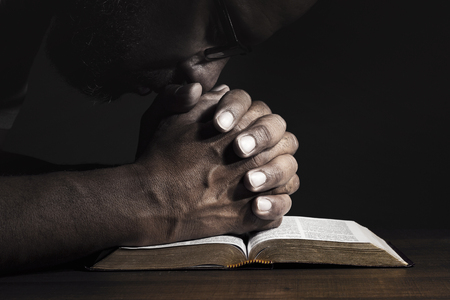 Photo for Man praying to God on a Bible in a dark place. - Royalty Free Image