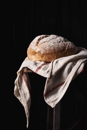 Foto de Composed loaf topped with flour on rustic kitchen towel with black background. - Imagen libre de derechos