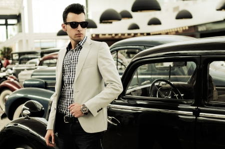 Foto de Portrait of a young handsome man, model of fashion, wearing jacket and shirt with old cars - Imagen libre de derechos