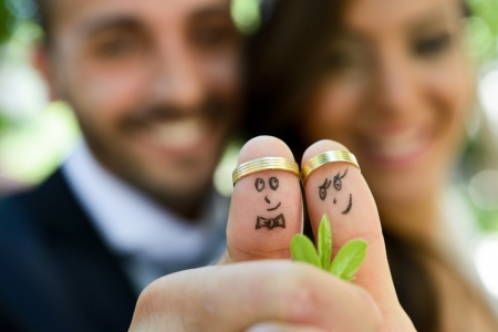 Foto de wedding rings on their fingers painted with the bride and groom, funny little people  - Imagen libre de derechos