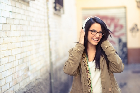 Photo for Portrait of young attractive girl in urban background hearing music with headphones - Royalty Free Image