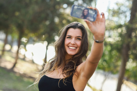 Foto de Portrait of a beautiful young woman selfie in the park with a smartphone - Imagen libre de derechos
